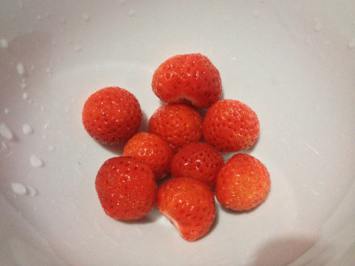 Today's strawberry harvest: 77 grams of Cambridge Favourite strawberries. Rinsed, tops removed, and placed in a bowl.